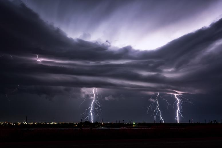 Three lightning bolts striking at the same time from a stormy night sky near Snyder, Texas