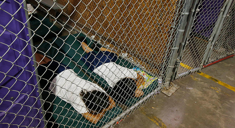 In this June 18, 2014 file photo, two female detainees sleep in a holding cell, as the children are separated by age group and gender, as hundreds of mostly Central American immigrant children are being processed and held at the U.S. Customs and Border Pr