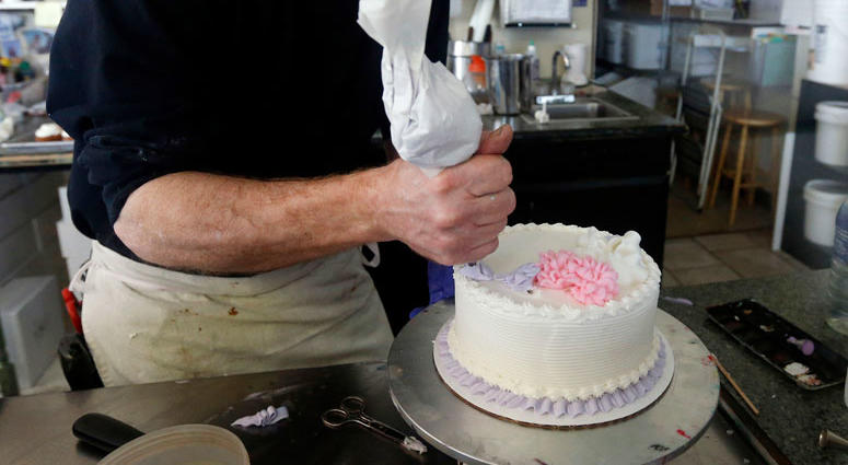 AP FILE - In this March 10, 2014, file photo, Masterpiece Cakeshop owner Jack Phillips decorates a cake inside his store in Lakewood, Colo.