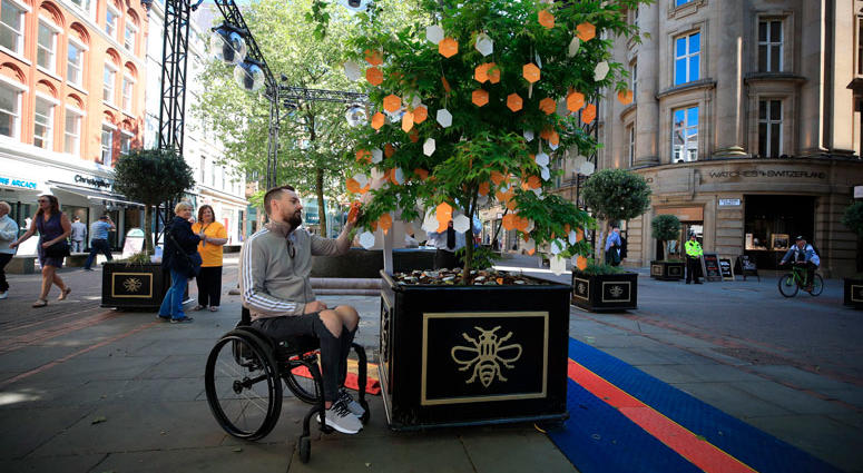 Martin Hibbertt, who suffered life-changing injuries in the Manchester terror attack, reads messages left on a 'Tree of Hope' in St Ann's Square, Manchester, England
