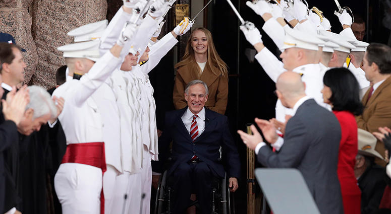 Texas Gov. Greg Abbott, front center, arrives for his inauguration ceremony with his daughter, Audrey, in Austin, Texas, Tuesday, Jan. 15, 2019.