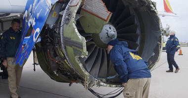 National Transportation Safety Board investigator examines damage to the engine of the Southwest Airlines plane that made an emergency landing at Philadelphia International Airport in Philadelphia.