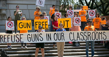 protesters gather on the West Mall of the University of Texas campus, in Austin, to oppose a new state law that expands the rights of concealed handgun license holders to carry their weapons on public college campuses