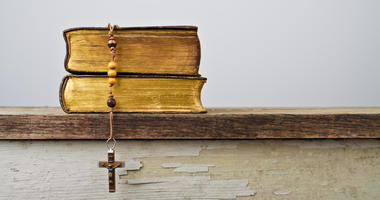 Rosary beads and books of Catholic Church liturgy