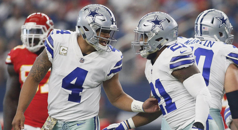 Dallas Cowboys quarterback Dak Prescott (4) tells running back Ezekiel Elliott