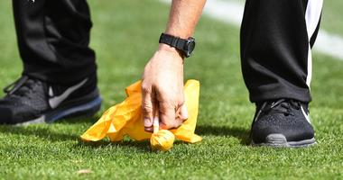NFL referee picking up a penalty flag