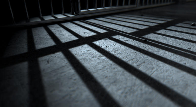 A closeup of view of a jail cells iron bars casting shadows on the prison floor
