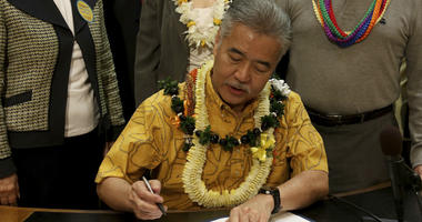 John Radcliffe, right, who was diagnosed with cancer in 2014, watches as Hawaii Gov. David Ige signs a bill to legalize medically assisted suicide on Thursday, April 5, 2018 in Honolulu.