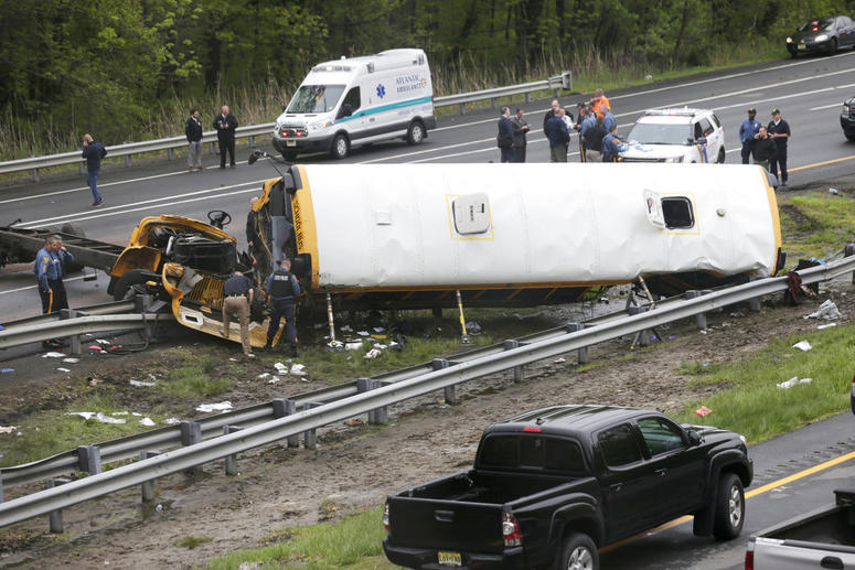 Emergency personnel work at the scene of a school bus and dump truck collision, injuring multiple people, on Interstate 80 in Mount Olive, N.J.
