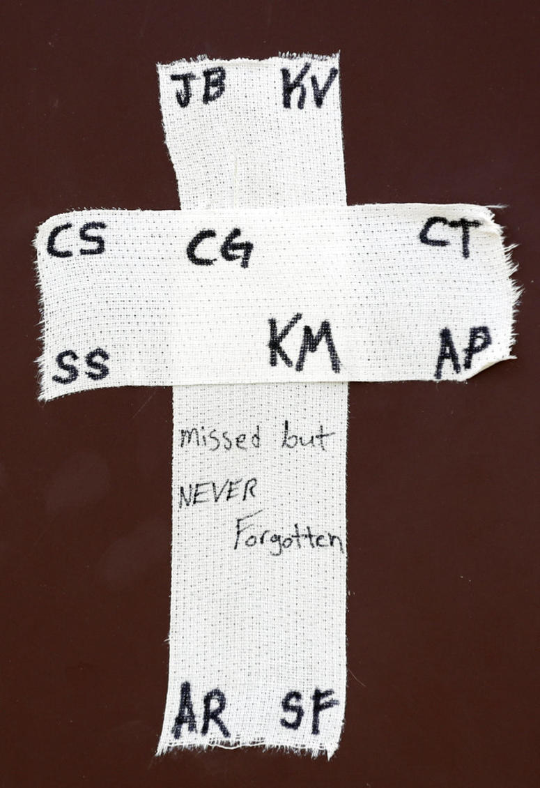 A tape cross with the initials of victims of the Santa Fe High School shooting is placed over the dugout of the Santa Fe baseball team before a baseball game against Kingwood Park High School.