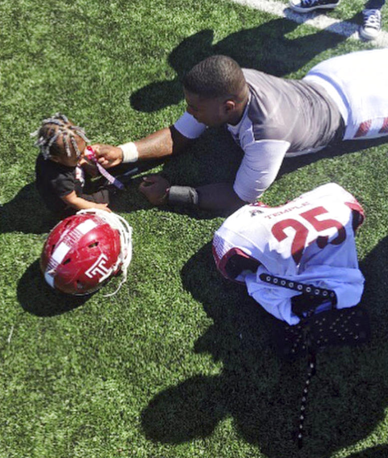 Temple running back Ryquell Armstead plays on the field with his daughter Ry-kail during spring NCAA college football practice in Philadelphia.