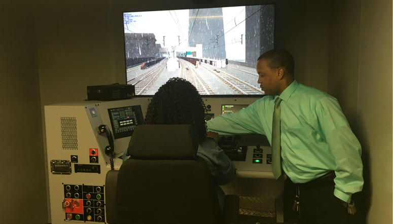 A SEPTA instructor guides a young student through paces to get her simulated passenger train out of 30th Street Station.