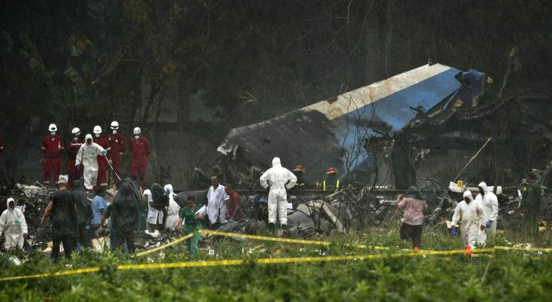 Rescue teams search through the wreckage site of a Boeing 737 that plummeted into a cassava field with more than 100 passengers on board.