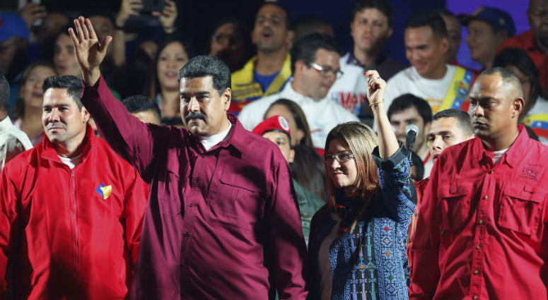 Venezuela's President Nicolas Maduro and his wife Cilia Flores wave to supporters after the National Electoral Council announced that with almost 93 percent of polling stations reporting, Maduro won nearly 68 percent of the votes in Sunday's election, bea