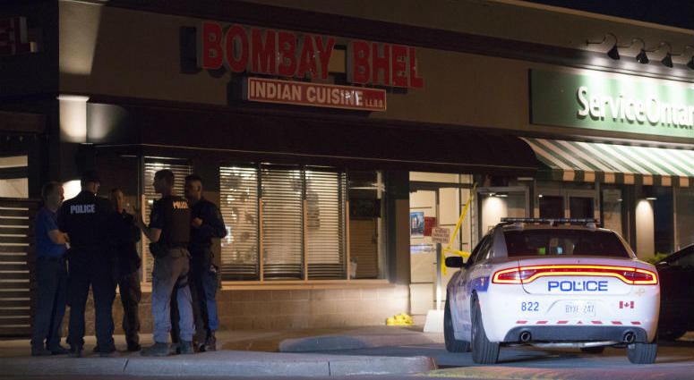 Police stand outside the Bombay Bhel restaurant in Mississauga, Canada Friday May 25, 2018. Canadian police say an explosion set off deliberately in a restaurant has wounded a number of people.