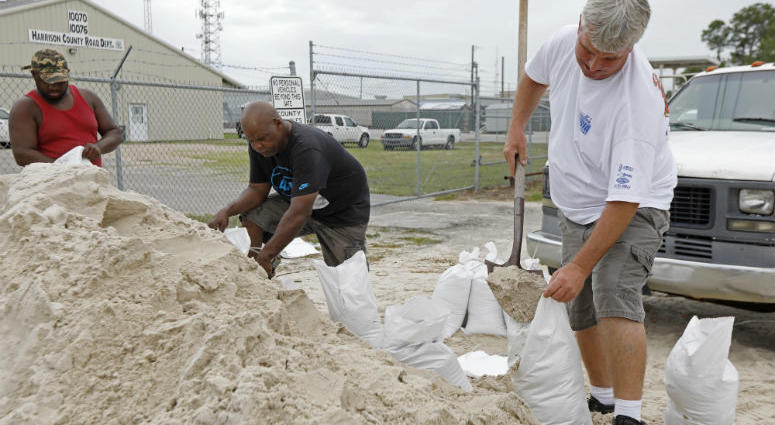 Gulfport, Miss., residents shovel sand into bags at a Harrison County Road Department sand bagging location, while preparing for Subtropical Storm Alberto to make its way through the Gulf of Mexico, Saturday, May 26, 2018.