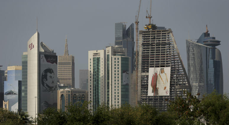 In this May 5, 2018 photo, the images of the Emir of Qatar, Sheikh Tamim bin Hamad Al Thani hang on the towers in Doha, Qatar.