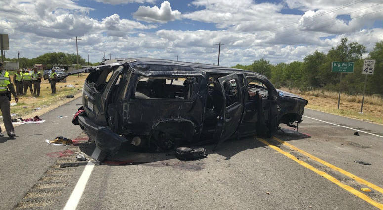 n this image tweeted by David Caltabiano of KABB/WOAI, a heavily damaged SUV is seen on Texas Highway 85 in Big Wells, Texas, after crashing while carrying more than a dozen people fleeing from Border Patrol agents, Sunday, June 17, 2018.