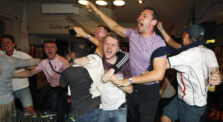 England supporters celebrate Harry Kane's winning goal as fans watch the World Cup soccer match between Tunisia and England at the Lord Raglan Pub in London.