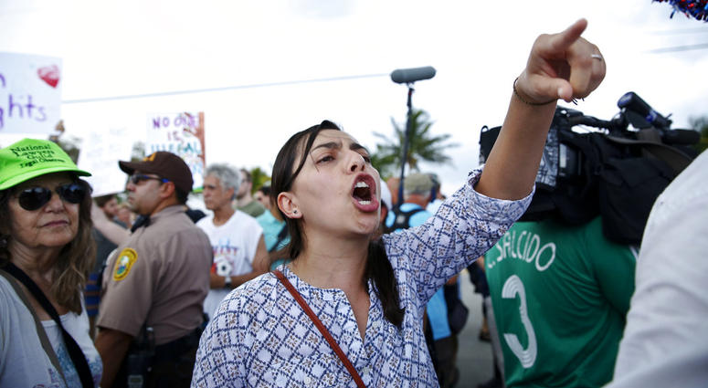 1 A protester yells toward a Trump supporter after arriving to the Homestead Temporary Shelter for Unaccompanied Children, on Saturday, June 23, 2018, in Homestead, Fla.