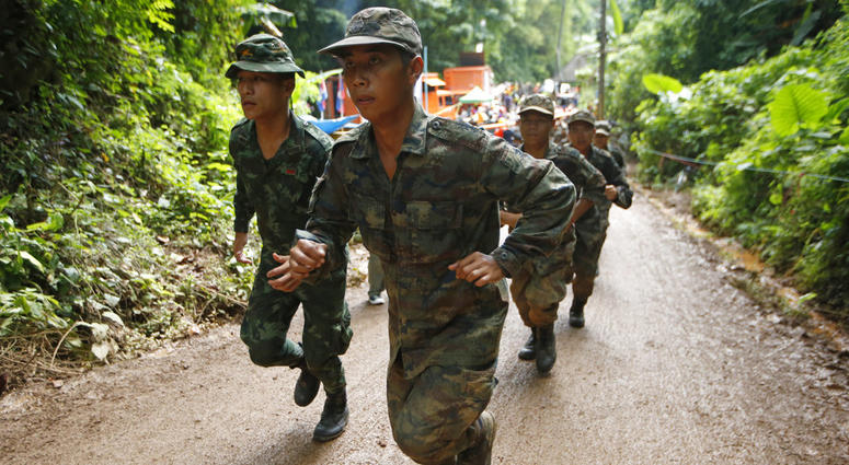 Thai soldiers make their way up at the entrance to a cave complex where 12 boys and their soccer coach has been trapped.