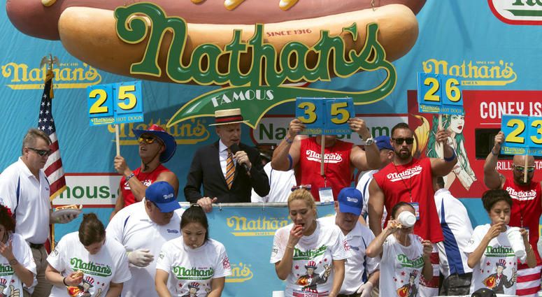 The competitors eat hot dogs during the women's competition of the Nathan's Famous Fourth of July hot dog eating contest, Wednesday, July 4, 2018, in New York's Coney Island.