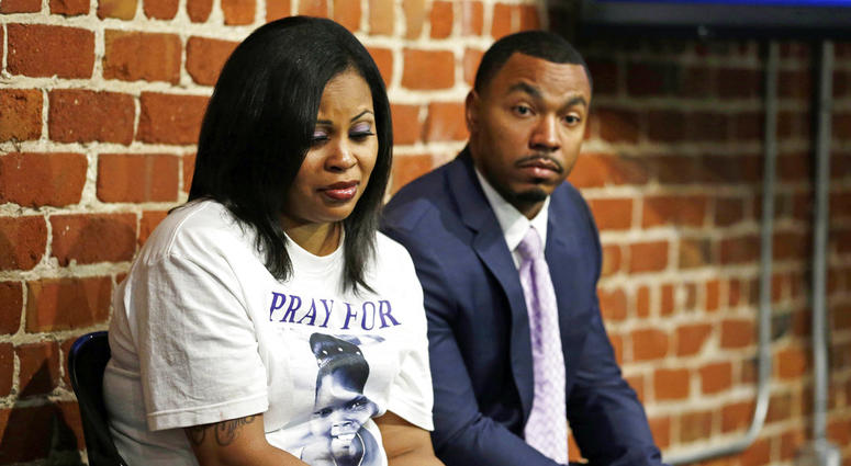 In this Oct. 3, 2014, file photo, Nailah Winkfield, left, and Omari Sealey, right, the mother and uncle of Jahi McMath, listen to doctors speak during a news conference in San Francisco.