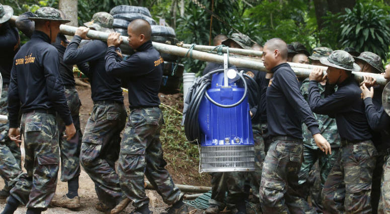 Pumps are moved from truck to be used to help drain the rising flood water in a cave where 12 boys and their soccer coach have been trapped since June 23, in Mae Sai, Chiang Rai province, in northern Thailand Friday, July 6, 2018.