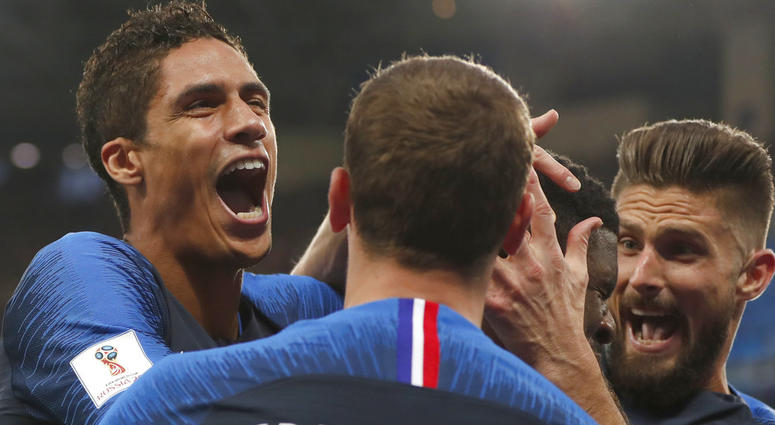 French players mob France's Samuel Umtiti after he scored the opening goal of the game during the semifinal match between France and Belgium at the 2018 soccer World Cup in the St. Petersburg Stadium.