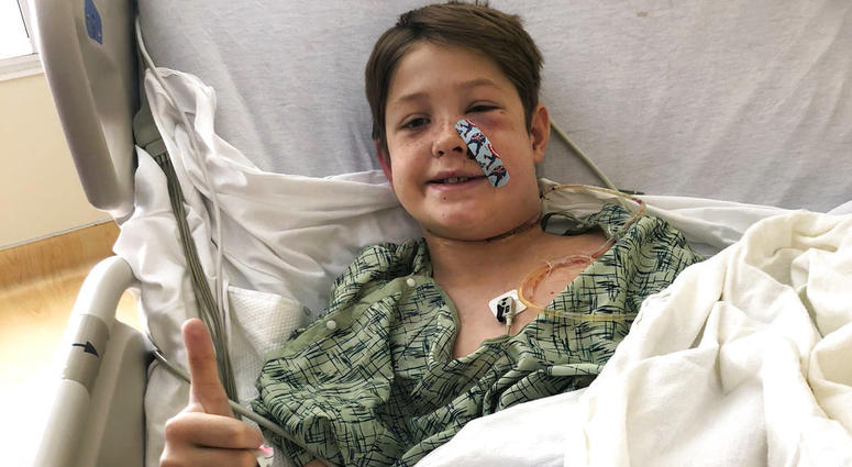 Xavier Cunningham, of Harrisonville, Mo., gives a thumbs up while recovering at the University of Kansas Hospital after surgery to remove a meat skewer that penetrated his skull from his face to the back of his head.