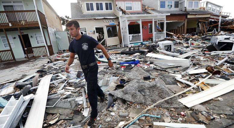 Firefighter Austin Schlarb performs a door to door search in the aftermath of Hurricane Michael in Mexico Beach, Fla., Thursday, Oct. 11, 2018.