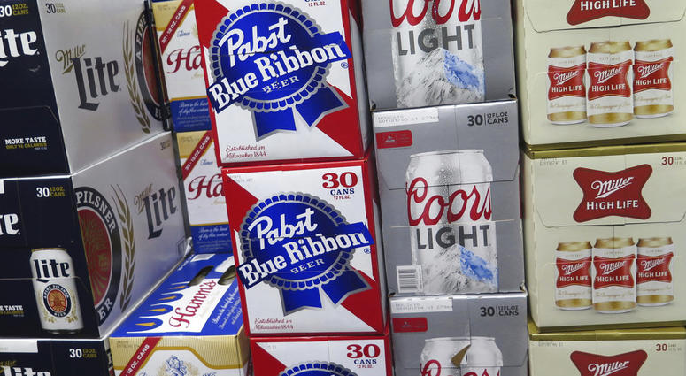 FILE - In this Nov. 8, 2018, file photo, cases of Pabst Blue Ribbon and Coors Light are stacked next to each other in a Milwaukee liquor store.