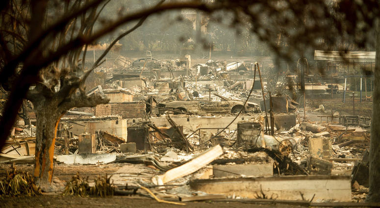 As the Camp Fire burns nearby, a scorched car rests by gas pumps near Pulga, Calif., on Sunday, Nov. 11, 2018.