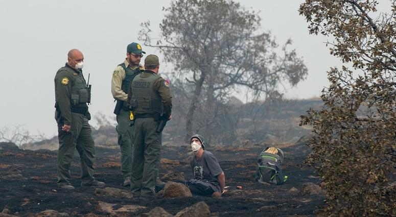 In this Thursday, Nov. 15, 2018, photo, Charlie Miles peers up at state forestry officers and state parks rangers after being arrested for trying to go home on a desolate stretch of Skyway Road between Paradise and a Chico church he was sleeping at.