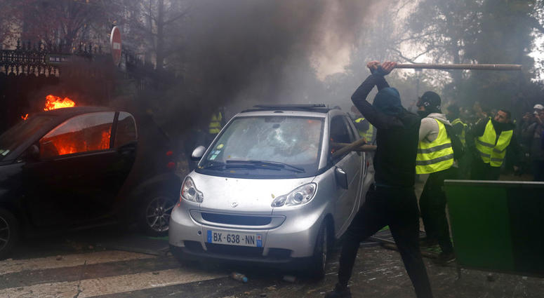 Hooded demonstrators smash a car during a demonstration Saturday, Dec.1, 2018 in Paris.