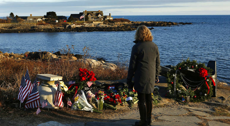 Cathy Rogers of Windham, Maine, pays her respects at a makeshift memorial for President George H. W. Bush across from Walker's Point, the Bush's summer home, Saturday, Dec. 1, 2018, in Kennebunkport, Maine.