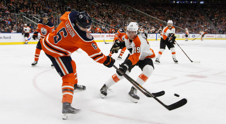 Philadelphia Flyers' Nolan Patrick (19) and Edmonton Oilers' Adam Larsson (6) battle for the puck during the third period of an NHL hockey game in Edmonton, Alberta, on Friday, Dec. 14, 2018.