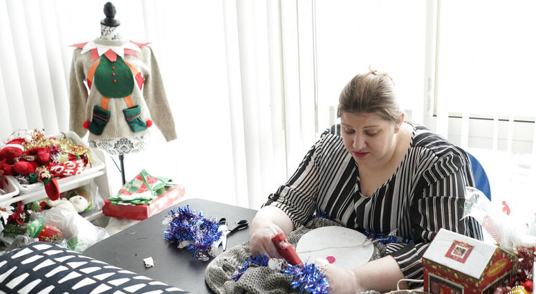 """Doris Cochran works on """"an ugly sweater,"""" which she is planning to sell. Cochran is a disabled mother of two young boys living in subsidized housing. She's stockpiling canned foods to ensure her family won't go hungry if her food stamps run out."""