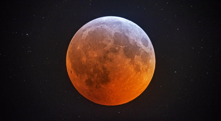 The totally eclipsed moon glows with a reddish color against the background stars.