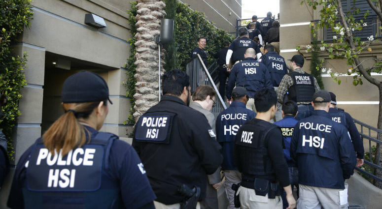FILE - In this March 3, 2015 file photo, federal agents enter an upscale apartment complex where authorities say a birth tourism business charged pregnant women $50,000 for lodging, food and transportation, in Irvine, Calif.
