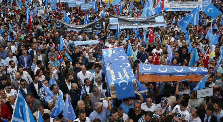 FILE - In this Saturday, July 4, 2015 file photo, Uighurs living in Turkey and their supporters, some carrying coffins representing Uighurs who died in China's far-western Xinjiang Uighur region, chant slogans as they stage a protest in Istanbul, against