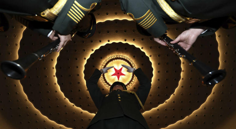A military band conductor rehearses the band before the closing session of the National People's Congress in Beijing's Great Hall of the People on Friday, March 15, 2019.