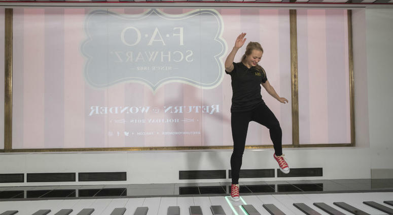 In this Tuesday, Nov. 13, 2018 photo, an employee plays the FAO Premium Piano Dance Mat during a media preview of the new FAO Schwarz store at Rockefeller Center in New York.