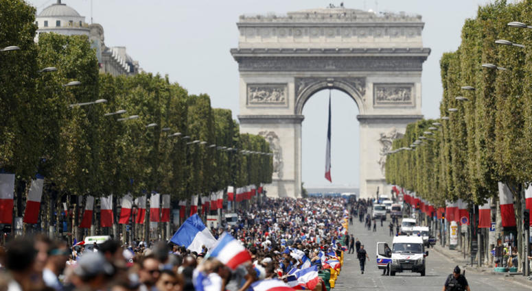 The crowd prepares to welcome the French soccer team for a parade a day after the French team victory in the soccer World Cup, Monday, July 16, 2018 in Paris.