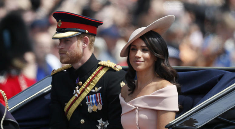 Britain's Prince Harry, left, and Meghan, Duchess of Sussex ride in a carriage to attend the annual Trooping the Colour Ceremony in London, Saturday, June 9, 2018.