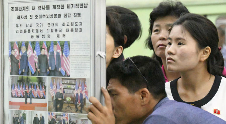 People look at the display of local newspaper reporting the meeting between North Korean leader Kim Jong Un and U.S. President Donald Trump, at a subway station in Pyongyang, North Korea Wednesday, June 13, 2018.