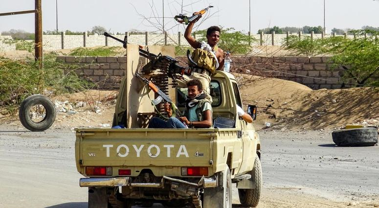 Pro-government forces cheer in the back of a pickup mounted with a machine gun outside Hodeidah.