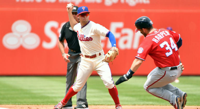 Philadelphia Phillies second baseman Scott Kingery (4) gets force out on Washington Nationals right fielder Bryce Harper (34) and throws to first base to complete double play during the second inning at Citizens Bank Park.