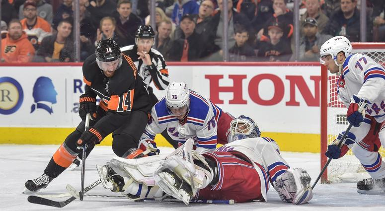Nov 23, 2018; Philadelphia, PA, USA; New York Rangers goaltender Henrik Lundqvist (30) falls on the puck as Philadelphia Flyers center Sean Couturier (14) attempts to score during the second period of the game at the Wells Fargo Center.