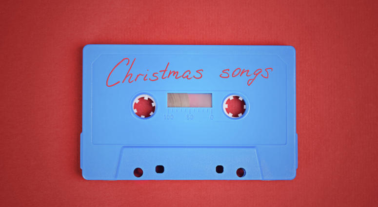 Blue audio cassette tape with christmas songs laying on red paper background